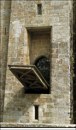 Que trouve-t-on en général derrière le pont-levis quand on entre dans le château ?