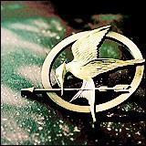 Qui donne à Katniss sa broche représentant un geai moqueur ?