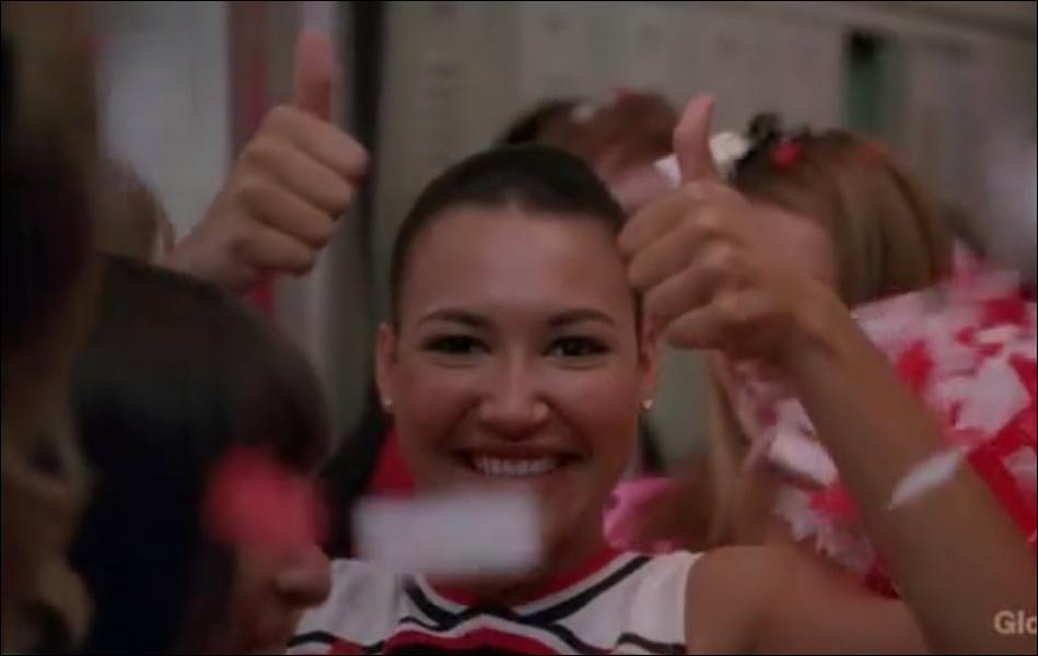 A qui Santana fait-elle signe quand le Glee Club revient vainqueur au lycée ?