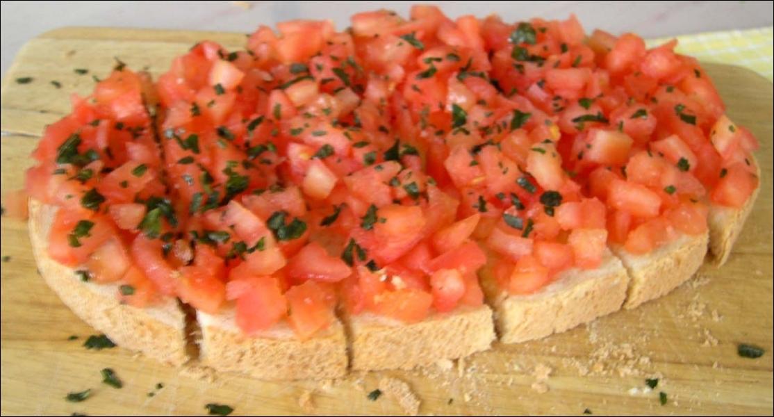 Il s'agit généralement d'une tartine de pain grillée frottée d'ail, arrosée d'huile d'olive et garnie de petits morceaux de tomates, assaisonnée de basilic :