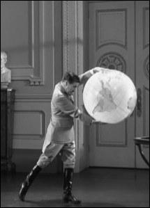 Dans la scène célèbre du globe terrestre où Chaplin joue avec celui-ci, comment finit la scène ?