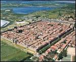 Quelle cité médiévale du sud de la France, enserrée à l'intérieur de remparts rectangulaires, fut un port fondé par St Louis au XIIIe siècle ?