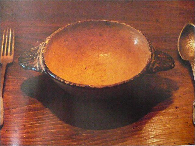 Une écuelle en terre cuite encadrée de couverts d'étain. Élément basique de la vaisselle paysanne jusqu'à la fin du XIXe siècle. Quelle est sa caractéristique ?