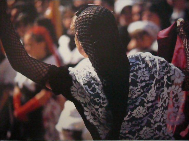 Femme vêtue d'un corsage brodé, et d'une jupe rouge. Sur les épaules, un châle de dentelle blanc ou noir. Aux pieds, les  bigatanes , pour danser allègrement la sardane aux pas rythmés.