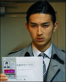 Fujimoto est un jeune homme chargé d'annoncer à certains jeunes gens qu'ils vont mourir dans les 24h à cause d'une injection qu'ils ont reçu dans leur enfance à cause d'une loi immonde. C'est :