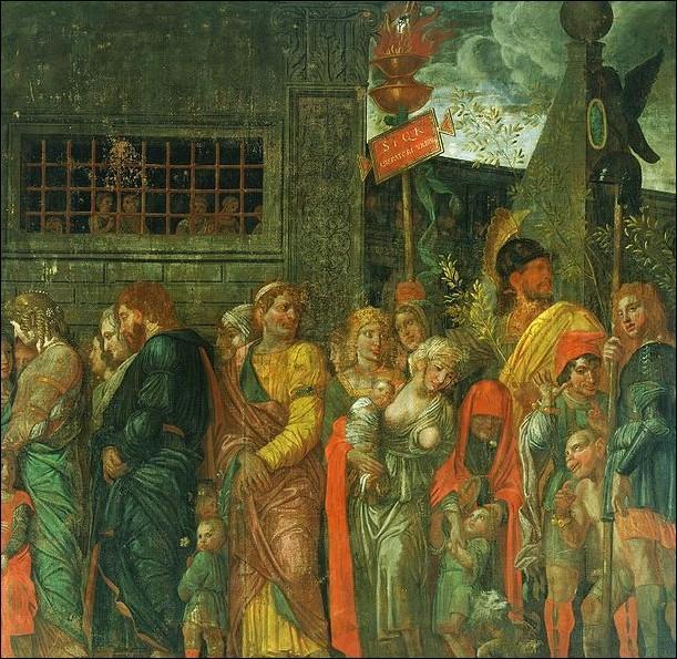 Quel personnage proche de Cléopâtre y assiste aussi, mais harnaché de chaînes, dans le défilé lui-même ?