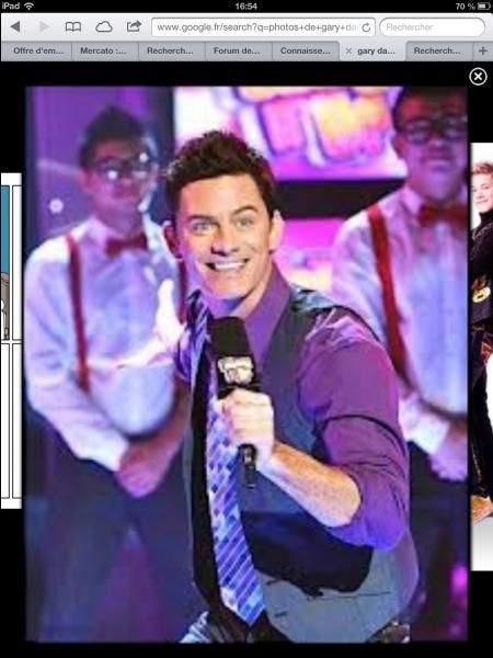 Comment s'appelle le présentateur de «Shake It Up» ?