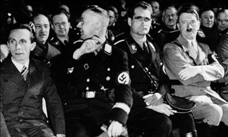 Était-il fou ? Plus probablement, c'était un simulateur. De plus, il a su en abuser. Malgré tout, il fut condamné à la prison à perpétuité pendant le procès de Nuremberg. Il se suicida en 1987. Sur la photo, c'est le personnage à côté d'Hitler. Qui est-il ?