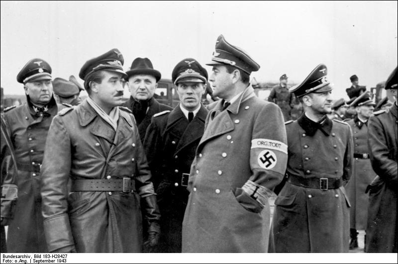 Au premier plan, vous pouvez voir deux personnages allemands. À gauche, le moustachu est un as de l'aviation nazie, surtout pendant la bataille d'Angleterre. À droite, avec un brassard, c'est l'architecte d'Hitler, responsable de l'organisation Todt et ministre de l'Armement. Qui sont-ils ?