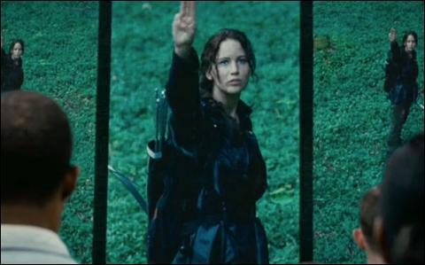 Lorsque Katniss prend la place de sa sœur à la Moisson, les citoyens du District 12 lui adressent un signe, trois doigts de la main droite portés à la bouche puis levés au ciel, signe que l'on reverra par la suite, notamment à la mort de Rue. Mais quel est ce signe dans le livre ?