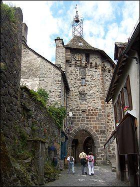 Quelle est cette ville située sur une butte basaltique du Cantal et célèbre pour ses vaches rouges et son fromage ?