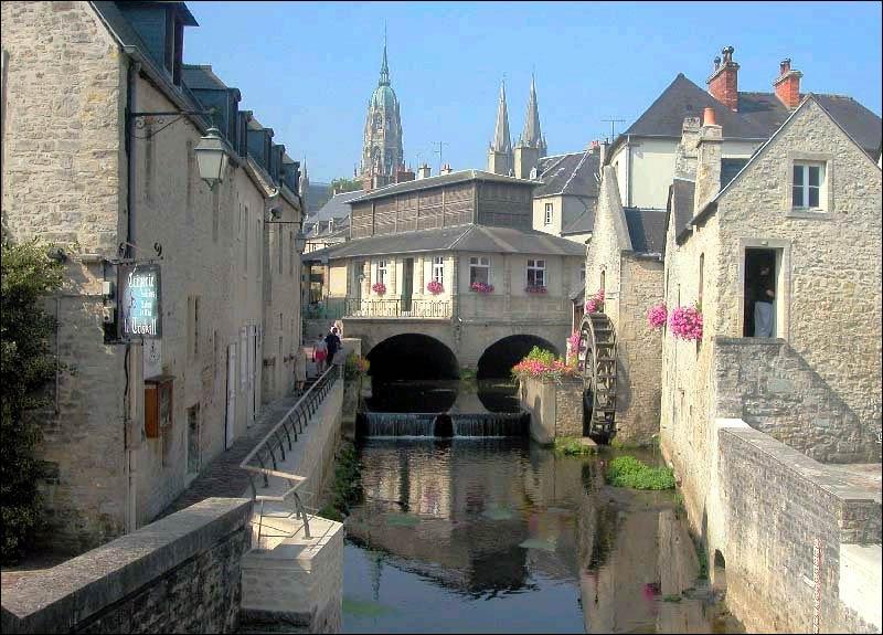 Située à quelques kilomètres des plages du Débarquement, dans le Calvados, elle a été la première ville libérée par l'opération Overlord. Sa cathédrale de style gothique a abrité la célèbre Tapisserie de la reine Mathilde.