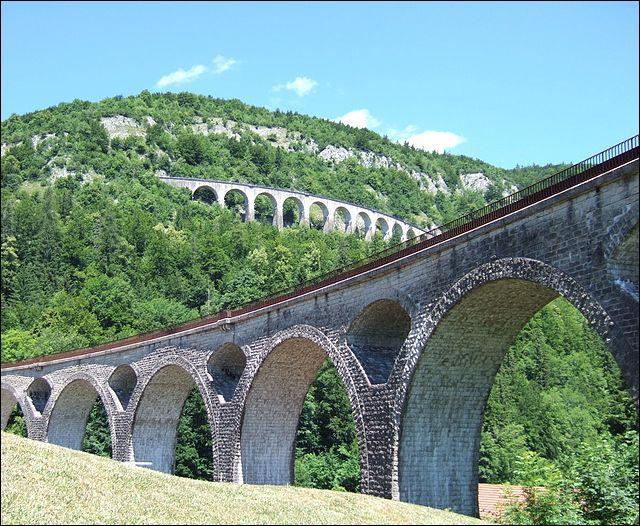 Ce viaduc ferroviaire courbe de 203 mètres de long et de 40 mètres de haut, enjambe la vallée de l'Evalude dans le Jura, à :