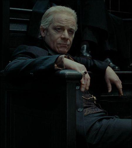 Alors qu'il vient à peine d'entrer dans le ministère, Ron Weasley (Reginald Cattermole) est pris à partie par le Mangemort Yaxley qui lui demande d'aller immédiatement dans son bureau. Que se passe-t-il ?