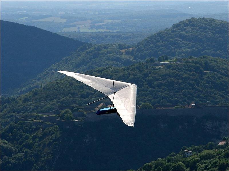 Le pilote d'un deltaplane est assis dans un harnais fixé au milieu de l'aile en forme de delta.