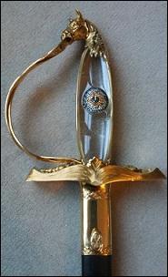 Regardez la garde de cette épée, c'est un livre ouvert qui porte sur ses pages, à gauche un caducée et à droite la main de chirurgien de ce membre. La fusée est en cristal de roche par évocation de la transparence de l'œil. Sur ce bloc de cristal est incrustée l'image d'un iris et d'une pupille (de Jacqueline, son épouse). Le pommeau représente la tête en or de son cheval Escorial. Ce bijou est à.