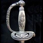 Cette épée ancienne, de membre de l'Institut d'Égypte, ayant appartenu au général Decouz, est faite d'argent doré, nacre, acier et cuir. L'épée, typique exemple de l'égyptomanie, est ornée d'un décor inspiré par l'art égyptien : figure féminine sur la fusée, tête de lion sur le quillon, palmiers, déesse Hathor. À quel historien d'art appartient-elle ?