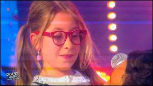"""C'est la plus petite du groupe, née le 27 avril 2007. C'est avec """"La vie en rose"""" d'Édith Piaf qu'elle a accédé aux battles de """"The Voice Kids 1"""". Il s'agit d'/de :"""
