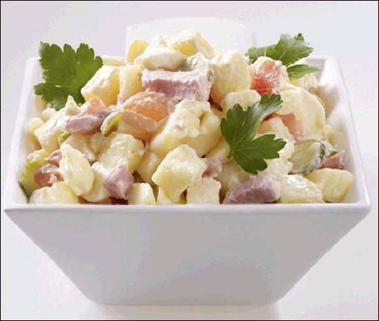 Même si la tomate n'est pas l'ingrédient principal de cette salade, elle s'y cache toutefois, bien que détrônée par la pomme de terre. On n'oubliera pas d'y glisser le jambon et les cornichons :