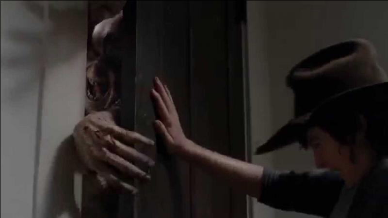 Après que Carl se soit fait attaquer par un rôdeur dans une maison, qu'écrit-il sur la porte ?